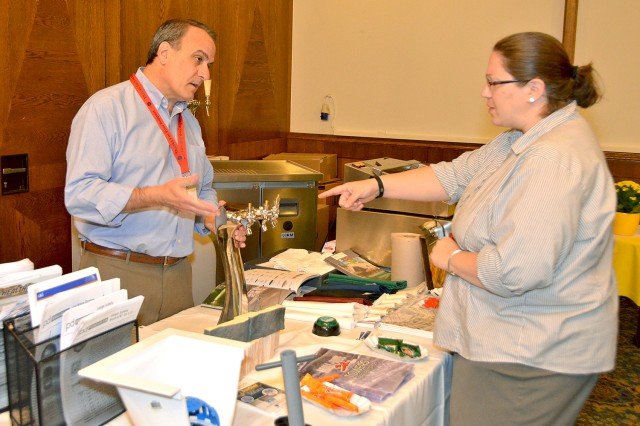 Jillian Singleton (right), a registered food and beverage specialist for the Installation Management Command-Europe, talks with Steven Goldstein, vice president of GKi, about various products available during the Trade Show.