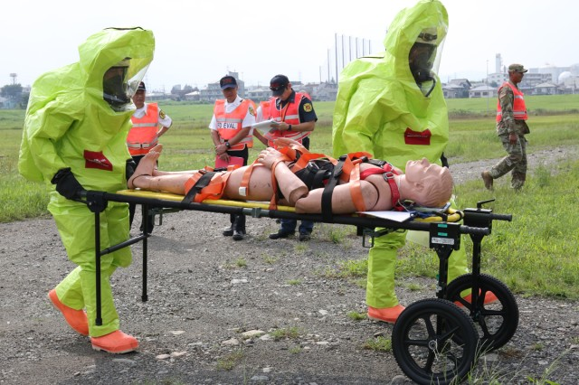 The first responders from Sagami General Depot's Directorate of Emergency Service for USAG Japan, rescue a chemically contaminated rubber dummy Aug. 21, 2017 during the USAG Japan's full-scale exercise on SGD. (U.S. Army photo by Noriko Kudo)