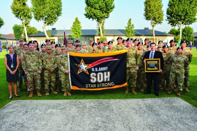 Brig. Gen. Dennis LeMaster, commander, Regional Health Command Europe, presents the Activity with the Safety and Occupational Health Star Flag and certificate in a ceremony on Hoekstra Field.