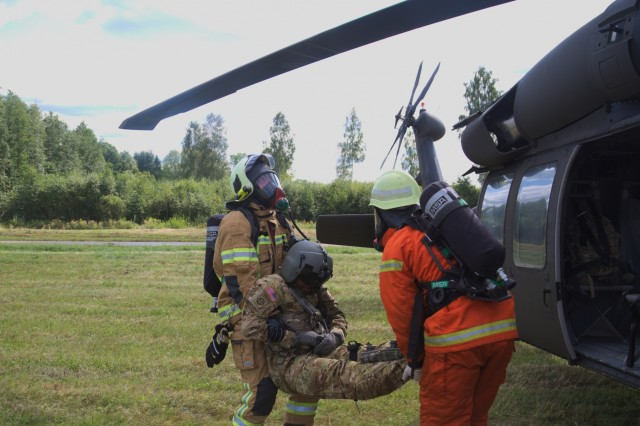 Latvian firefighters safely carry Chief Warrant Officer 3 Doug Patterson, a UH-60 Black Hawk pilot with 3rd General Support Aviation Battalion, 10th Aviation Regiment, 10th Combat Aviation Brigade, 10th Mountain Division, during an air disaster exercise at Lielvarde Air Base, Latvia on August 29, 2017. American and Latvian forces are working together in Latvia as a part of Operation Atlantic Resolve, a NATO mission involving the US and its European Allies and partners in a combined effort to enhance bonds of friendship and promote peace. (Photo by Army Pfc. Nicholas Vidro, 7th Mobile Public Affairs Detachment)