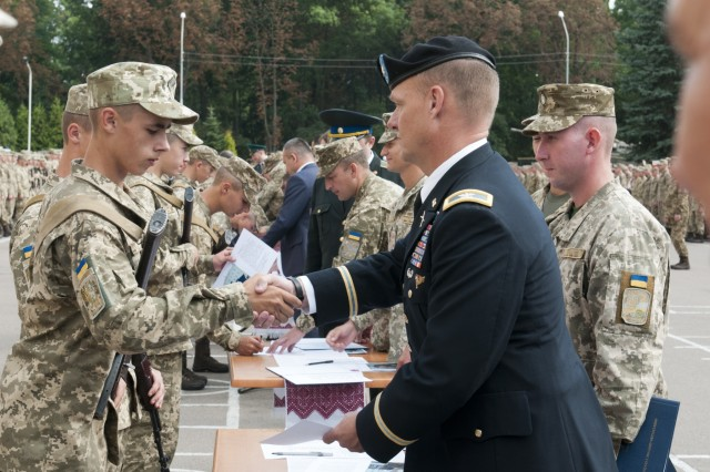 Col. Charles Booze, the deputy commanding officer of the 45th Infantry Brigade Combat Team and chief-of-staff for the Joint Multinational Training Group - Ukraine, congratulates a graduating cadet of the Hetman Petro Sahaidachny National Army Academy in Lviv, Ukraine, on Aug. 26.The 45th IBCT is deployed to Ukraine as part of the Joint Multinational Training Group - Ukraine at the Yavoriv Combat Training Center on the International Peacekeeping and Security Center, west of Lviv. The JMTG-U is a coalition of nations dedicated to improving the professionalism within the Ukrainian army. (Photo by Staff Sgt. Eric McDonough, 45th Infantry Brigade Combat Team)