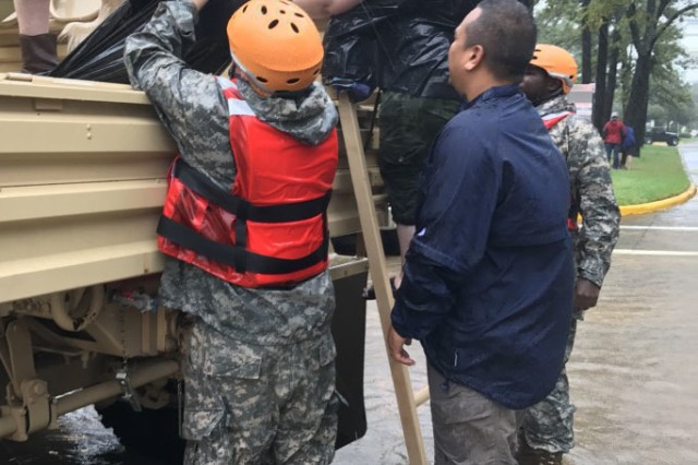 Texas Guard members from the 386th Engineer Battalion and a local volunteer help children from a military vehicle in Cypress Creek, Texas, August 29, 2017. An extended National Guard response is expected.