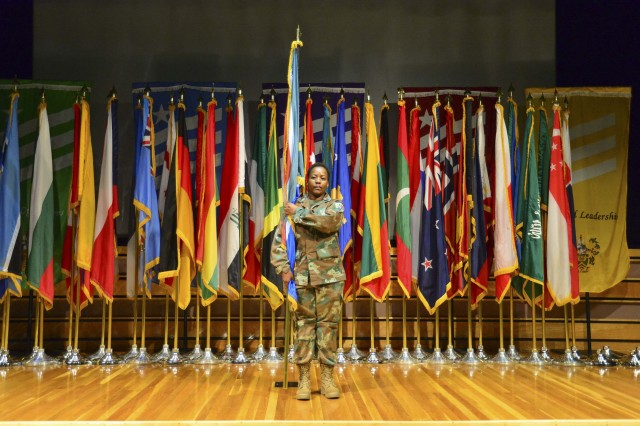 Master Sgt. Sophie Mokgadi Madigage, from the South African Army, presents her country's flag August 28, during opening ceremonies of Sergeants Major Course Class 68. Madigage joins the 58 other international students who make up the largest class of internationals in the history of the Sergeants Major Course.
