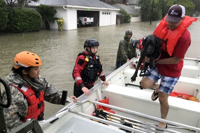 Texas Guardsmen from the 386th Engineer Battalion, first responders from Texas Task Force One and the Cypress Creek Fire Department move residents from severely flooded neighborhoods to safety days after Hurricane Harvey in Cypress Creek, Texas, Aug. 28, 2017. The team rescued more than 1,000 people and hundreds of dogs and cats, bringing them to dry ground.