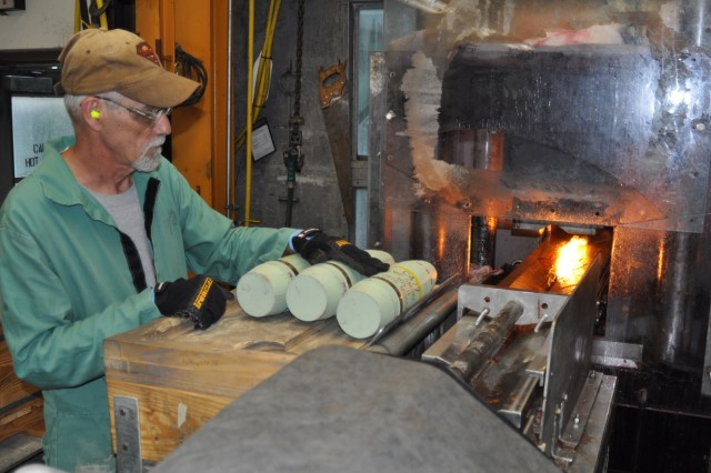 Once the red phosphorous is extracted, it goes through the same conversion process as white phosphorous to become phosphoric acid. The phosphoric acid is then sold as agricultural fertilizer and the metal is sent to be locally recycled.  Pictured here, a Crane Army Ammunition Activity employee prepares white phosphorus canisters to go through the conversion process.