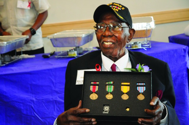 Richard Bell, a 99-year-old veteran and Blackstone resident, poses for pictures with medals he earned more than 72 years ago in World War II during a family reunion event Aug. 26 at the Eastern Henrico Recreation Center near Richmond.  Bell was a participant in the Red Ball Express logistical operation during the war.  Bell's great nephew and former reporter Benjamin Sessoms Jr. discovered a year ago his relative never received awards pertaining to his military service and initiated efforts for a formal presentation. Congressman Dave Brat along with Brig. Jeffrey Drushal, Chief of Transportation at Fort Lee, presented the medals.