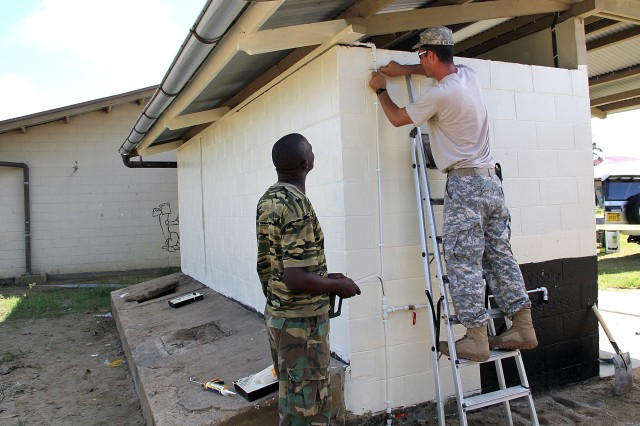 U.S. Army Staff Sgt. Louis Du Randt, right, 211th Engineer Company, South Dakota Army National Guard, and a Suriname Army soldier conduct renovation work at the O.S. 1 Santo Dorp School in Wanica, Suriname, Aug. 11, 2016. The renovation project was conducted as part of the Suriname and South Dakota State Partnership Program to provide training for military construction personnel while simultaneously assisting in a worthy community need.