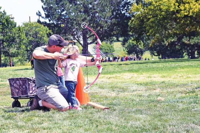 Kylee Goodall, daughter of Chief Warrant Officer Jake Goodall of 3rd Assault Helicopter Battalion, 1st Aviation Regiment, 1st Combat Aviation Brigade, 1st Infantry Division, holds form as her dad helps guide arrow to target Aug. 26. The family archery range was one of many free amenities open to Fort Riley's community, service members and their families for the grand opening of the park between 11:30 a.m. to 7 p.m. Aug. 26.