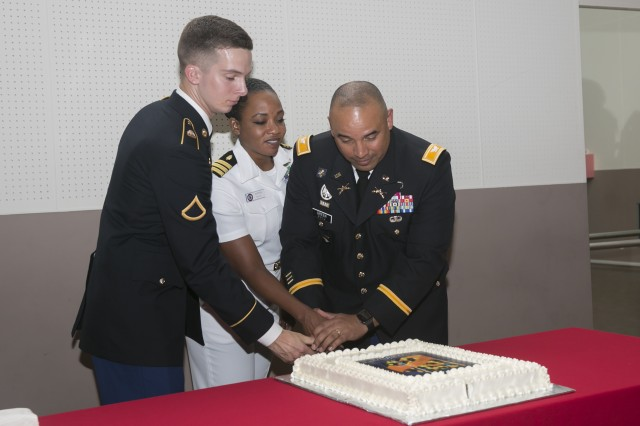 From left to right: Pfc. Joshua Ball, Navy Cmdr. Sonya Waters, and Col. Darrell Green cut the cake following the Women's Equality Day Observance held Aug. 24, 2017 at the Camp Zama Community Recreation Center. (U.S. Army photos by Honey Nixon)