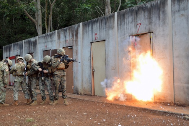 Combat engineers from the 29th Brigade Engineer Battalion, 3rd Brigade Combat Team, 25th Infantry Division, and Marines from the 2nd Battalion, 3rd Marine Regiment, brace themselves during a live explosive door breaching at Schofield Barracks, Hawaii, on Aug. 30, 2017. Army combat engineers and Marines trained together on a variety of door breaching techniques. (U.S. Army photo by Staff Sgt. Armando R. Limon, 3rd Brigade Combat Team, 25th Infantry Division)