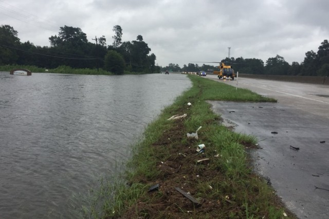 A U.S. Coast Guard rescue helicopter sits on I-10 in Orange, Texas, August 30, 2017. Texas National Guard soldiers, service members from the U.S. Coast Guard and Texas Task Force 1 and Austin-Travis County Emergency Medical Service swift water rescue technicians worked together to rescue a man with special medical needs from high-rising waters and medically evacuate him to a safe location.