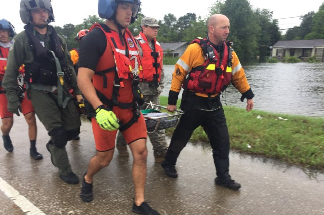 Texas National Guard soldiers, service members from the U.S. Coast Guard and Texas Task Force 1 and Austin-Travis County Emergency Medical Service swift water rescue technicians work together to rescue a man with special medical needs from high-rising waters and medically evacuate him to a safe location, in Orange, Texas, August 30, 2017. Thousands of first responders from the military and local, state and federal agencies joined together to render aid to all those endangered by the high-rising floodwaters in south Texas following Hurricane Harvey.