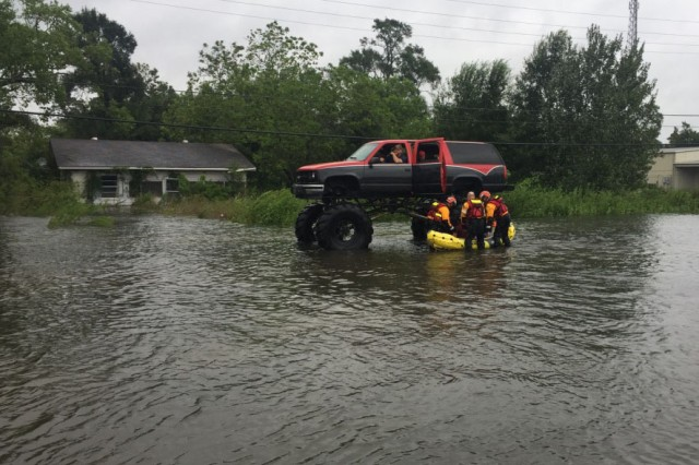 A volunteer driving a monster truck stops Texas National Guard soldiers and Texas Task Force 1 and Austin-Travis County Emergency Medical Service swift water rescue technicians, offering to assist in evacuating anyone endangered by the flooding to a safe location, Orange, Texas, August 30, 2017. Thousands of first responders from the military and local, state and federal agencies joined together alongside thousands of volunteers, to render aid to all those endangered by the high-rising floodwaters in south Texas following Hurricane Harvey.