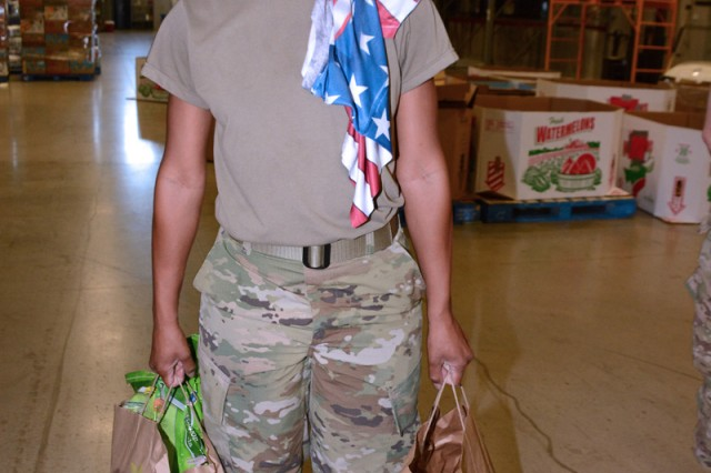 With a donated American flag shirt draped over her shoulder, Captain Latrina Dudley poses with two bags of items at the San Antonio Book Bank warehouse.