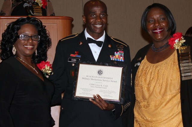 New York Army National Guard Command Sgt. Major Corey Cush, center, receives an award from the national Blacks in Government organization during their annual dinner in Atlantic City, New Jersey, on August 22, 2017. Cush, the command sergeant major of the New York Army National Guard's 53rd Troop Command, received the Blacks in Government Military Meritorious Service Award.  With are (left) Darlene H. Young, the organization's past President and Dr. Doris Sartor, the president of BIG.