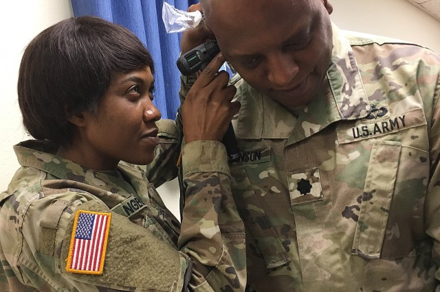 Spc. Martha Ngenue, an ear, nose and throat specialist with the Carl R. Darnall Army Medical Center Preventive Medicine Clinic, checks the ear canal for obstructions and ear plug size for Lt. Col. Brian Robinson, a senior planner with the U.S. Army Operational Test Command's Operations Directorate, during OTC's safety stand down Aug. 30.