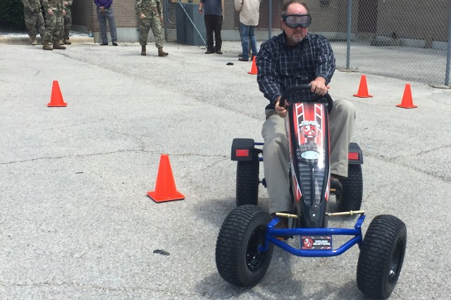 """Kevin O. Kruise, a U.S. Army Operational Test Command operations officer, starts to navigate a cone course while wearing """"drunk goggles"""" during the unit's command safety stand down Aug. 30."""