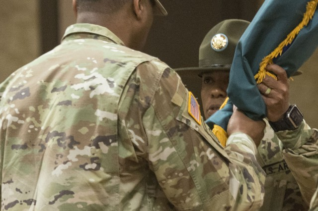 Command Sgt. Maj. Michael L. Berry takes the U.S. Army Drill Sergeant Academy colors from Command Sgt. Maj. Michael Gragg during a ceremony Aug. 31 at the Fort Jackson NCO Club. At the ceremony Berry took command of the institution that trains drill sergeants.