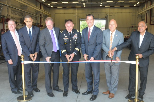 The U.S. Army Reserve's 99th Regional Support Command hosted a ribbon-cutting ceremony Aug. 17 for the Area Maintenance Support Activity, Organizational Maintenance Shop, on Fort Totten, New York. Major Gen. Troy D. Kok, commanding general of the 99th RSC, center, cut the ribbon at the revitalized facility in Fort Totten. U.S. Congressman Thomas R. Suozzi and New York City Council Member, 19th District, Queens, Paul A. Vallone are third and second from right. The center underwent a $12.6 million full-facility revitalization, allowing technicians to perform in an up-to-date facility to meet readiness standards as well as train military unit mechanics as needed so they can perform maintenance while they're deployed.