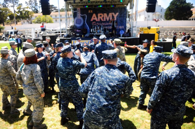 "PRESIDIO OF MONTEREY, California -- Soldiers, Sailors and Airmen groove out to the tunes of DJ Jena Red during Army Entertainment's ""United We Band"" show at Soldier Field, July 21."