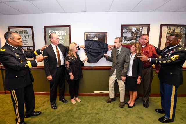 The Long family unveil the plaque dedicating the room to Major Long. (Left to Right) LTG Aundre F. Piggee, Dr. Greg Yarrow, Mrs. Tina Yarrow, Mr. George Long, Mrs. Michelle Stevens, Mr. Wes Stevens, and SGM Edward Bell.
