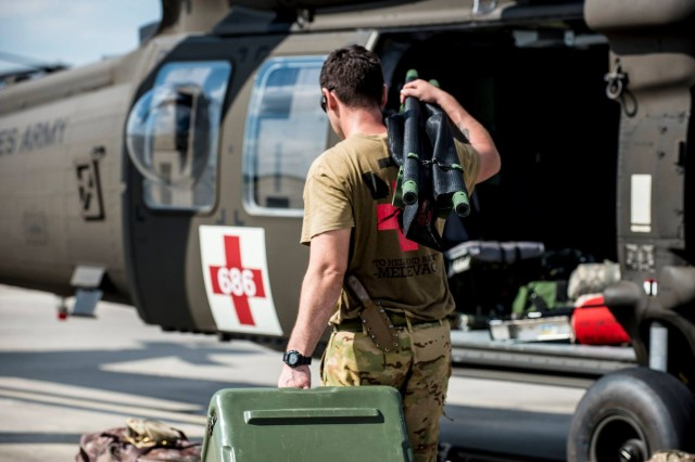 A Soldier with Company C, 1st Battalion, 111th Aviation Regiment loads his aircraft with medical supplies and other equipment on the tarmac at Cecil Field. Throughout the Florida National Guard's response to Hurricane Irma, these UH-60 Blackhawks stand ready for medical evacuations.