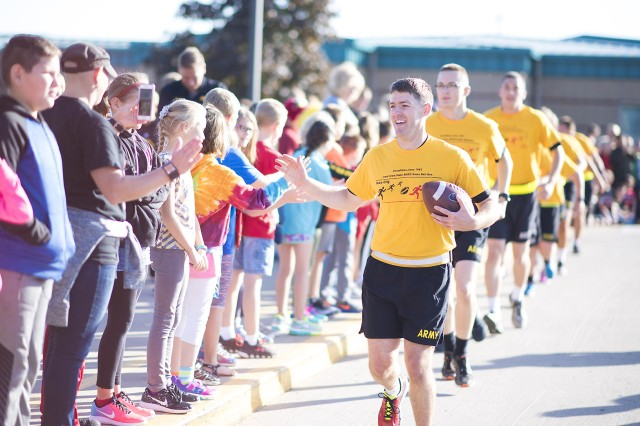 Cadet Nathan Dittner, University of Iowa ROTC battalion commander, leads the way with the Cyclone-Hawkeye game ball during the annual Game Ball Run Sept. 8 at Williamsburg Elementary School, Williamsburg, Iowa.