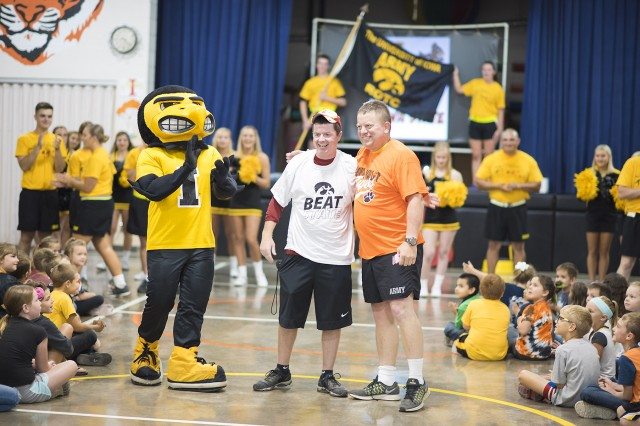 "Lt. Col. Zach Buettner (right), professor of military science, University of Iowa ROTC, ""converts"" an Iowa State University Cyclone fan by convincing him to put on a U of I shirt during a pep rally at Iowa Valley Elementary School, Marengo, Iowa."