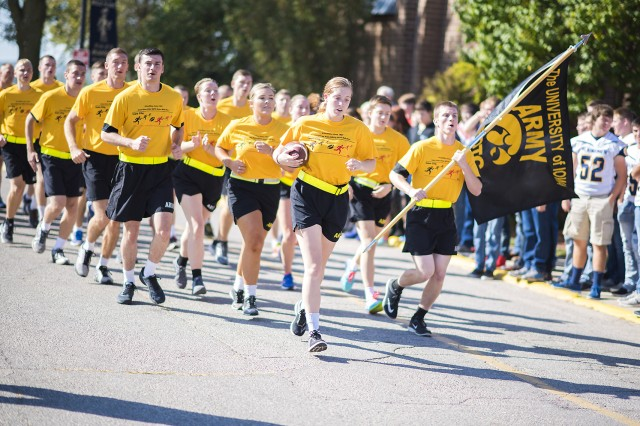 Cadet Erin Lingal, University of Iowa ROTC, leads the way with the Cyclone-Hawkeye game ball during the annual Game Ball Run Sept. 8 at Belle Plaine High School, Belle Plaine, Iowa.