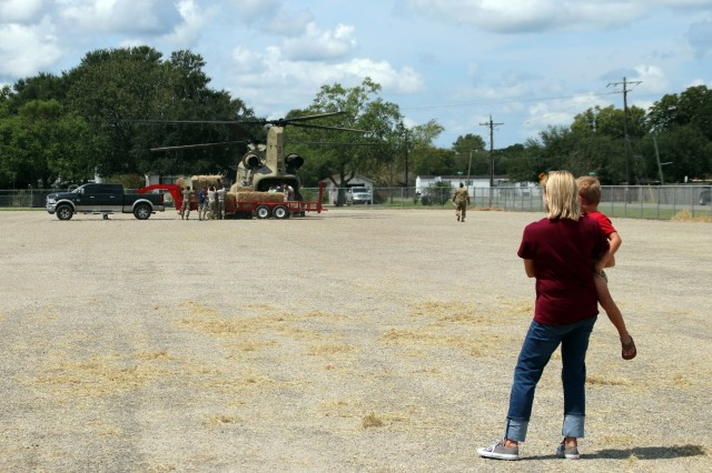 Soldiers and Airmen from the Texas Military Department loading hay bales onto Chinook helicopters are joined by civilians in Hamshire, Texas, September 5, 2017. Texas Military Forces are using air assets to support local cattle ranchers protect their herds from starving, by air dropping hay bales to flooded areas.