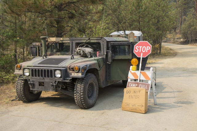 A Humvee belonging to the 443rd Signal, of the Montana National Guard, is parked in front of a checkpoint at the entrance to Lolo National Forest, in Florence, Mont., on September 9 2017. The National Guard is manning various checkpoints around fires to free up Law Enforcement Personnel.