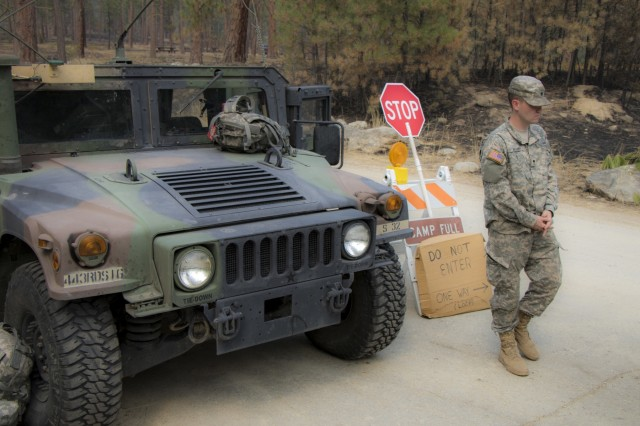 Spc. Brown, of the 443rd Signal, stands in front of his humvee at the entrance to Lolo National Forest, Florence, Mont. on September 9, 2017. Soldiers are activated for 15 days at a time to ensure the safety of the public.