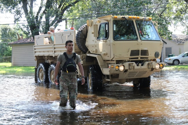 Pvt. Juan Retana of the 3-133rd Field Artillery ground guides a vehicle through flood waters. Texas Army National Guard Soldiers from the 36th Infantry Division transported and distributed food, water, and supplies from Orange County Airport to stranded residents in low-income areas of Orange, Texas on September 6th, 2017.