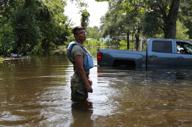 Pvt. Andres Lopez of the 3-133rd Field Artillery ground guides a Light Medium Tactical Vehicle through flood waters. Texas Army National Guard Soldiers from the 36th Infantry Division transported and distributed food, water, and supplies from Orange County Airport to stranded residents in low-income areas of Orange, Texas on September 6th, 2017.