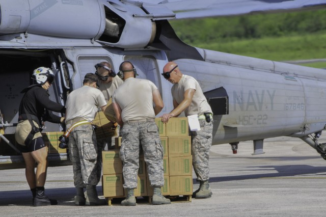 Members of the 164th Logistics Readiness Squadron, Tennessee Air National Guard, and a US Navy Petty Officer 2nd Class Aviation Warfare Specialist, load Federal Emergency Management Agency emergency rations on to a UH-60L Black Hawk helicopter at an air terminal near St. Croix's airport, Sept. 9. In a joint effort, Soldiers, Airmen and Navy members moved personnel and tremendous amounts of cargo from St. Croix to St. Thomas and St. John to aid Hurricane Irma recovery relief.