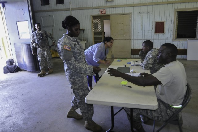 Spc. Symone Simon, a member of the 662nd Engineer Company, Virgin Islands National Guard presents her military identification for manifest documentation at the Aerial Terminal Operations Center during Joint Reception, Staging, Onward Movement, and Integration at an aerial port terminal near St. Croix's airport, Sept. 9. Thirty-six members of the Virgin Islands National Guard and Tennessee and Rhode Island Air National Guard moved personnel and tremendous amounts of cargo from St. Croix to St. Thomas and St. John to aid Hurricane Irma recovery relief.