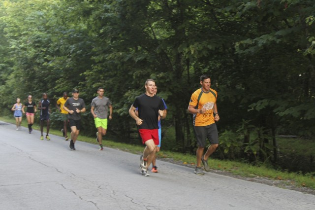 Capt. Josh Joseph (front right), commander for Headquarters and Headquarters Company, 101st Special Troops Battalion, 101st Airborne Division (Air Assault) Sustainment Brigade, 101st Abn. Div., and another member of the Fort Campbell, Kentucky Ten Miler Team, lead a group of runners, Aug. 3, 2017, during practice trail run on Fort Campbell, Kentucky.