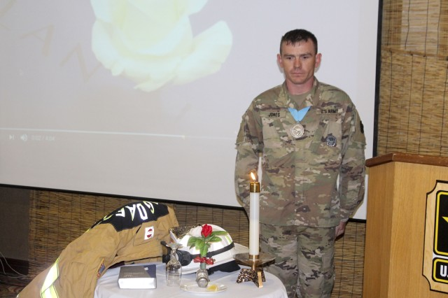 Staff Sgt. Jones, a member of Area IV Audie Murphy Club overlooks the table of the fallen comrade during the 9/11 Remembrance Luncheon, Sept. 8, 2017 at the Camp Walker Evergreen Club.