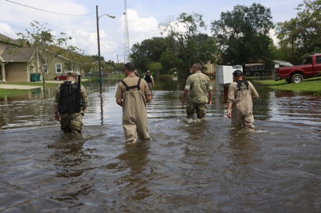 U.S. Soldiers from the 1st Squadron, 124th Cavalry Regiment, FBI and local law enforcement walk through the streets checking on the residents affected by Hurricane Harvey, Orange, Texas, Sept. 5, 2017. Police and U.S. Soldiers work together with the focus of helping residents in flooded areas and those in need of help in surrounding areas.