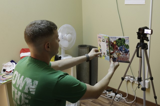 20170910-A-RW053-014 Staff Sgt. Christopher Gilkison, paralegal NCOIC for the 371st Sustainment Brigade, shows the page he is reading to a camera for his kids at USO's United Through Reading Program on Camp Arifjan, Kuwait on September 10, 2017. (U.S. Army photo by Sgt. 1st Class Charles Highland)