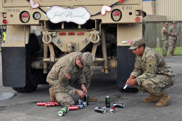"Oklahoma Army National Guard Soldiers, Spc. Cameron Bernard, left, and Spc. Edgar Trujillo, serving with A Company, 1st Battalion, 79th Infantry Regiment, 45th Infantry Brigade Combat Team, tie empty soda cans to the back of a transport vehicle at Regional Support Area Beaumont, Texas, Sept. 12, 2017. While the 45th Infantry Brigade Combat Team was in Texas in support of Hurricane Harvey recovery efforts, two of their fellow Soldiers exchanged vows. This is their ""getaway"" vehicle."