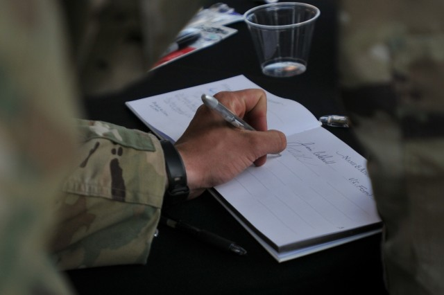 A Soldier from 1st Battalion, 79th Infantry Regiment, 45th Infantry Brigade Combat Team, Oklahoma Army National Guard, signs a registry Sept. 12, 2017, after the wedding of two Oklahoma National Guard Soldiers deployed to Beaumont, Texas, for Hurricane Harvey recovery operations.