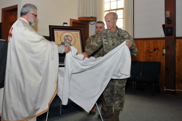 Col. Phil Deppert, commandant of the Defense Language Institute Foreign Language Center, Presidio of Monterey, California, and Father George Khoury, associate professor of Levantine at the Institute, unveil the St. Jerome icon in the Presidio Chapel Sept. 11. The icon will be displayed in the Aiso Library on the Presidio. St. Jerome became inducted as the patron saint of DLI and of military linguists. Linguists now join with other military career fields who have followed in this tradition. (U.S. Army photo by Patrick Bray/Released)