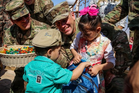 2nd Lt. Ty Roberts from the 35th Infantry Division, helps hand out school supplies and candy to children of the Khalileh Tribe during a community engagement event near the King Abdullah II Special Operations Training Centre, Aug. 18, 2017. The project was a cooperation between U.S. service members in Jordan and the Jordan Armed Forces -- Arab Army aimed at building strong relationships between the armed forces and local community members.