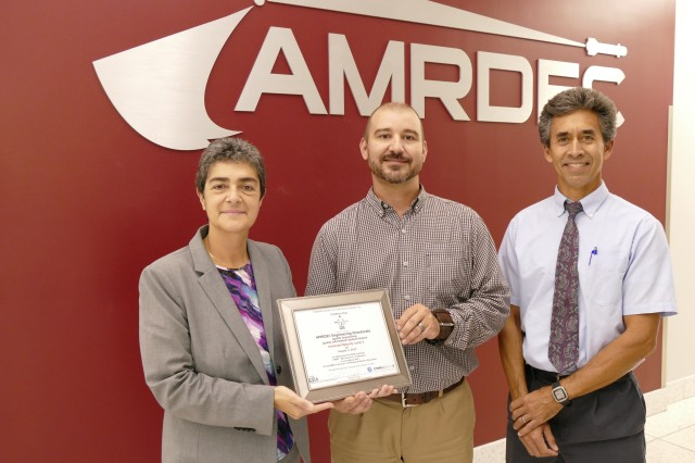 Sandra Cepeda, president of Cepeda Systems & Software Analysis, Inc., presents a certificate of CMMI level three appraisal to QIS Branch Chief, Trey Lawler and Chief of Quality Engineering, Derec Roby.