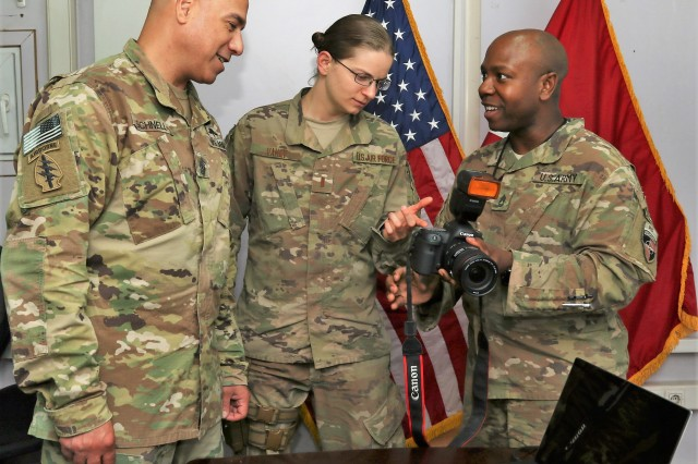 Sgt. 1st Class E. L. Craig (right) describes some of the new digital imaging equipment recently received by Combined Security Transition Command -- Afghanistan, to the organization's senior enlisted leader, Command Sgt. Maj. Bryan Schnell (left) and Air Force 2nd Lt. Dana Vahey (center), one of the organization's collateral duty Public Affairs officers. Craig, who serves as CSTC-A's Public Affairs senior noncommissioned officer, explains how this equipment will enable the PAO office to better communicate the CSTC-A and Resolute Support missions.