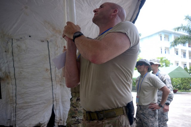 Oregon National Guard Tech. Sgt. Eric Hubbard, team leader and training Non-Commissioned Officer in Charge for the 142nd Fighter Wing Explosive Ordnance Disposal unit, helps lift a tent in place in preparation for the 2017 Disaster Management Engagement Activity (DMEA) held in Hanoi, Vietnam. Hubbard and other members of the Oregon National Guard's CBRNE Enhanced Response Force Package (CERFP) along with U.S. Marine Corps III Marine Expeditionary Force worked together during a week long exercise to share information and tactics for chemical disaster response with their partners in Vietnam's National Committee for Incident, Disaster Response, and Search and Rescue (VINASARCOM).