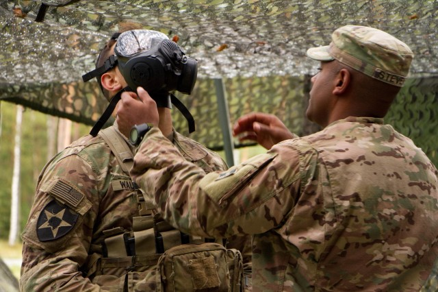 A candidate from 2d Cavalry Regiment is tested on his ability to don his protect mask correctly. Here the grader is checking for a proper seal Sept. 12, 2017 on the Patrol Lane during 2CR Expert Infantry Badge testing week in the Grafenwoehr Training Area, Germany. The Regiment hosted the EIB training and test week Sept. 6 -- 15. Candidates must pass, to standard and time, an Army Physical Fitness Test, day and night land navigation, 30 tasks, 12-mile ruck march and the Objective Bull event.