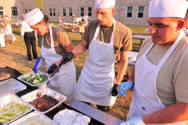 "From left, Warrant Officer Sarah Zadoyko of New Jersey, Sgt. Jake Roberts of Maine, and Pvt. Alex Morse of New Hampshire, teamed as the ""Granite Grillers,"" compete in the ""Iron Chef"" competition held during the NHNG's second annual food service training exercise Sept. 11 at the Edward Cross Training Complex in Pembroke, New Hampshire."