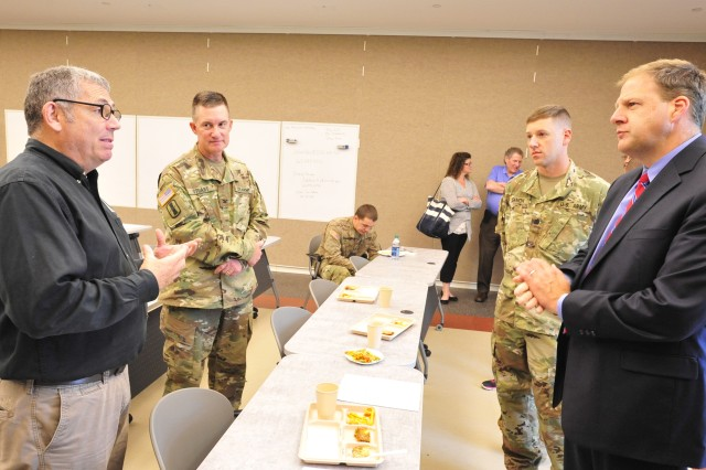 New Hampshire Governor Chris Sununu (far right) speaks with Stephen Moody (far left), director of the Combat Feeding Directorate at the Natick Soldier Research, Development and Engineering Center, during a demonstration/sampling of recent ration advances. The demonstration was part of a Joint Service Tactical Field Feeding Exercise held at the Departments of the Army and Air Force Joint Force Headquarters, New Hampshire National Guard, in Concord, New Hampshire.